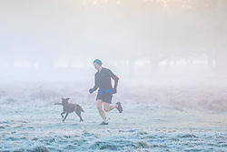 © Licensed to London News Pictures. 18/01/2020. London, UK. Runner enjoys the fog this morning as dog walkers and families enjoy a wonderful frosty and misty morning in Richmond Park, London. Forecasters predict a cold week ahead as Richmond Park issued a warning for ice after the previous day's high rain fall which could lead to increased slippery conditions for walkers and road users. Photo credit: Alex Lentati/LNP