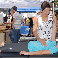Chiropractor from the Nutrition Healing Center, Claudy-Ann Keasberry works on Gina Samas  during the Santa Monica Chamber of Commerce's 26th Annual Health and Fitness Festival at the Third Street Promenade on Saturday, July 30, 2011.