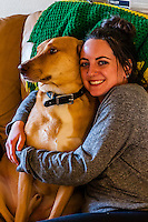 Young woman relaxing at home with her dog, Aurora, Colorado USA.