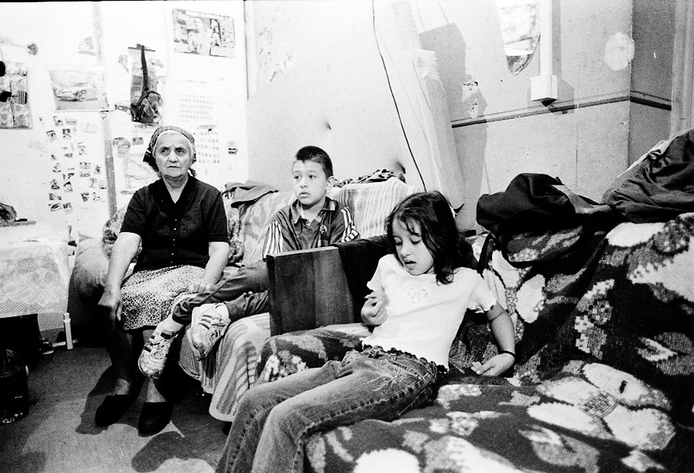 Anja, Dejan and their grand-mother inside their cubicle...The Krstic family left Kosovo after they were threatened to have their house burnt. They are sharing a warehouse with another 20 families where only thin partitions divide one room from the other. Anja and Dejan go to the local school but feel their only friends are in the camp. They feel rejected by the other children at school. They are seen as being different even if they are Serbs. ...During the summer1999, over 245,000 Serbs and Roms fled to Serbia and Montenegro from or within Kosovo in fear of reprisals from the majority Albanian population, after NATO air strikes had forced the withdrawal of Yugoslav. In 2003, less than 2% of them had returned and a large number of these internally displaced persons (IDPs) were still living in camps in very difficult conditions..In addition, around 5,000 IDPs, mainly of Roma ethnicity, are living in unrecognized collective centres, makeshift huts, corrugated metal containers and other substandard shelters. .This work  meant to look at how the life of children and young adults is affected by the fact that they are IDPs. I asked myself more specifically what would be different for these children/young adults from the 'normal' people of their age as far as education, health, social life, family, 'love' life and leisure are concerned. ...Anja, Dejan et leur grand-mère dans leur 'cabine'..La famille Krstic a quitté le Kosovo après qu'on les ait menacé de brûler leur maison. Ils partagent un entrepôt avec 20 autres familles séparées entre elles par des cloisons très fines.  Anja et Dejan vont à l'école locale mais se sentent rejetées par leurs compagnons de classe. Ils sont vus comme étant 'différents' même s'ils sont serbes...Pendant l'été 1999, plus de 245 000 serbes et roms ont fuit le Kosovo pour chercher refuge en Serbie ou au Montenegro, par peur de représailles de la part de la majorité de la population albanaise après que les forces de l'OTAN aient forcé l'armée you
