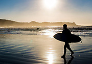 TOFINO, B.C. (01.01.16) – A surfer walks along the beach at Cox Bay near Tofino, B.C. after a sunset surf on New Year's Day. Photo by Marissa Tiel