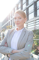 Portrait of confident businesswoman standing arms crossed outside office building