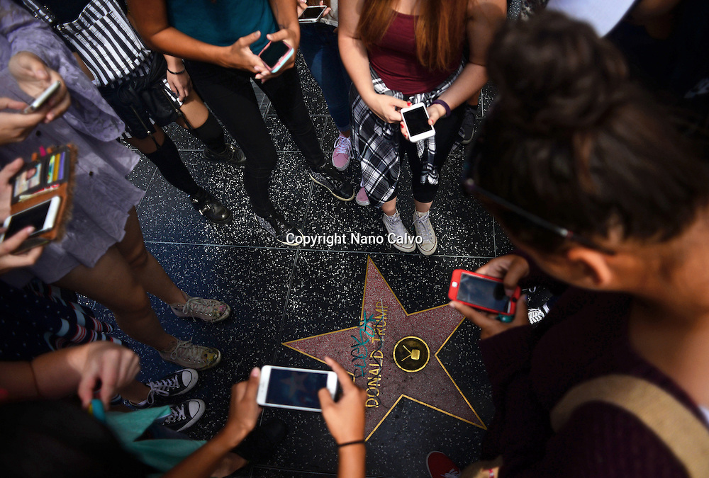 Teenagers taking photo of ruined Donald Trump star at Hollywood Walk of Fame, Los Angeles.