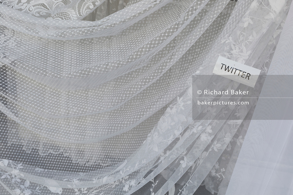 A detail of net curtains called Twitter, in the window of a home furnishings business, on 31st March 2019, in Faversham, Kent, England.