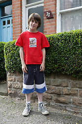 Boy standing outside his house in the street,