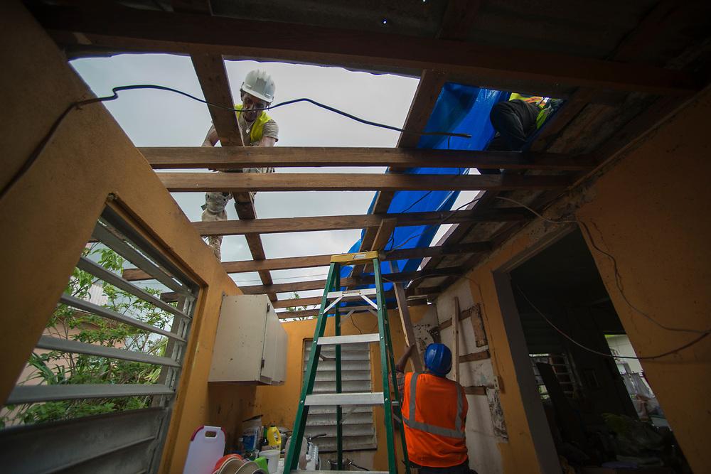 Punto Santiago, PR--FEMA subcontractos replace a damaged tarp on a home in Punto Santiago, PR, Novembe 9, 2017. Photo by Lori Waselchuk/braf.org