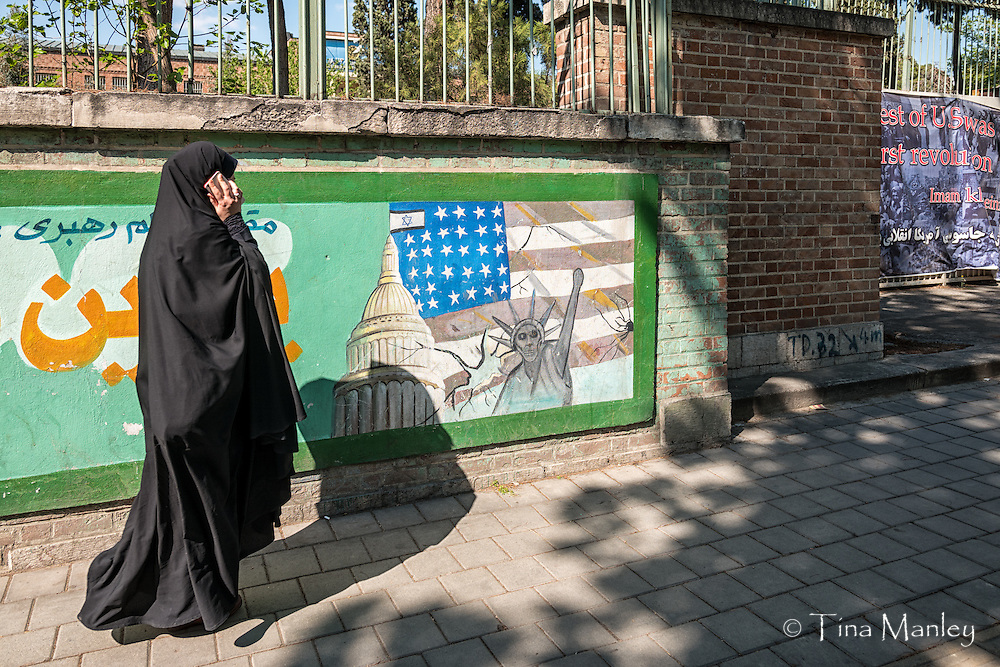 Woman in chador, talking on cellphone, walks past anti-American signs in front of the former American Embassy in Tehran, Iran.