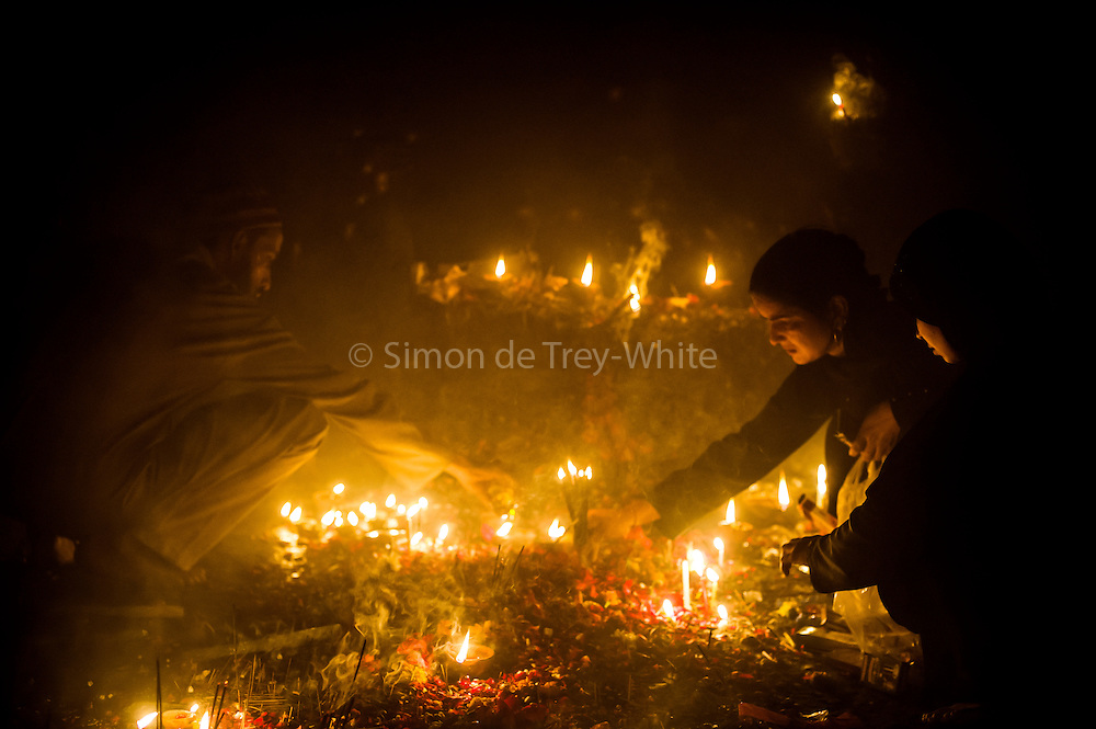 20th November 2014, New Delhi, India. Believers pray, make offerings and ask for wishes to be granted by Djinns in the ruins of Feroz Shah Kotla in New Delhi, India on the 20th November 2014<br /> <br /> PHOTOGRAPH BY AND COPYRIGHT OF SIMON DE TREY-WHITE a photographer in delhi<br /> + 91 98103 99809. Email: simon@simondetreywhite.com<br /> <br /> People have been coming to Firoz Shah Kotla to leave written notes and offerings for Djinns in the hopes of getting wishes granted since the late 1970's. <br /> Feroz Shah Tughlaq (r. 1351&ndash;88), the Sultan of Delhi, established the fortified city of Ferozabad in 1354, as the new capital of the Delhi Sultanate, and included in it the site of the present Feroz Shah Kotla. Kotla literally means fortress or citadel. The pillar, also called obelisk or Lat is an Ashoka Column, attributed to Mauryan ruler Ashoka. The 13.1 metres high column, made of polished sandstone and dating from the 3rd Century BC, was brought from Ambala in 14th century AD under orders of Feroz Shah. It was installed on a three-tiered arcaded pavilion near the congregational mosque, inside the Sultanate's fort. In centuries that followed, much of the structure and buildings near it were destroyed as subsequent rulers dismantled them and reused the spolia as building materials.