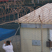 """A detainee looks out from the fence surrounding his cell in Camp 4 at the detention facility in Guantanamo Bay, Cuba. Camp 4 is a communal style camp where more compliant detainees live in small groups and have access to a more open air environment. Approximately 250 """"unlawful enemy combatants"""" captured since the September 11, attacks on the United States continue to be held at the detention facility.(Image reviewed by military official prior to transmission)"""