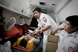 10:44 AM A severly injured motorcycle driver is rushed to hospital. On the night shift: Bangkok's body collectors. Paid per casualty, private ambulance crews race through the Thai capital on a nightly hunt for the injured and deceased.<br /> <br /> Every night in the Thai capital, dozens of private ambulance teams roam the streets and alleys of the sprawling mega-city of south-east Asia to collect the injured and the dead. The city has an average of four violent crimes and three fatal road accidents reported each hour of the night; there is no shortage of work.<br /> <br /> Thailand does not have a state-run emergency system, and most hospitals lack rescue vehicles and emergency room resources. For the most part, the ambulance teams are funded by private foundations, based in Bangkok's Chinatown, which operate on donations. The main ambulance squads, such as the Poh Teck Tung Foundation and Ruam Katanyu Foundation, are in fierce competition.