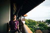 A staff prepares an outdoor terrace overlooking the ocean at the Holiday Inn Resort Benoa in Bali, Indonesia.