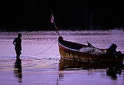 Young boy getting boat from anchorage at dawn for a days fishing - Boca Chica, Panama.