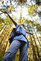 A low angle view of a woman looking up and spreading her arms wide celebrating the natural beaty around her, Little Si trail, Washington, USA.