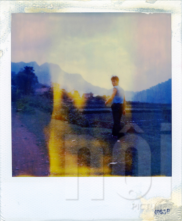 A vietnamese man walks along the road and turns his back to look the photographer. Northern Vietnam, Asia. The polaroid is really outdated and present a yellow trace on its surface.