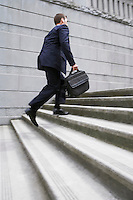 Business man carrying briefcase ascending steps