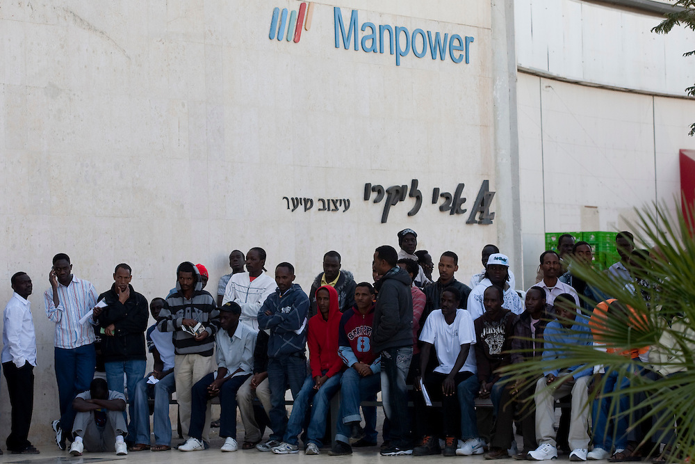 "Sudanese refugees wait outside the Immigration and Borders Authority to receive a visa in the city of Eilat on  February 27 2011. The municipality hung 1,500 red flags around the city as a sign of warning and put up hundreds of banners reading: ""Protecting our home, the residents of Eilat are drawing the line on infiltration."" Eilat Mayor Meir Yitzhak Halevi said that 10 percent of the city's population was currently made up of migrants and that the residents feel that the city has been conquered...Photo by Olivier Fitoussi."