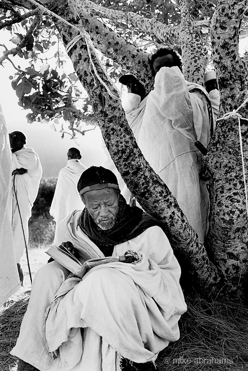 Ethiopian Orthodox pilgrims at Lalibela, Ethiopia. Monks in private prayer during the festival of Timkat (Epiphany). Lalibela in northern Ethiopia is famous for it's monolithic roack hewn churches and is one Ethiopia's holiest cities and a centre of pilgrimage for much of the country.