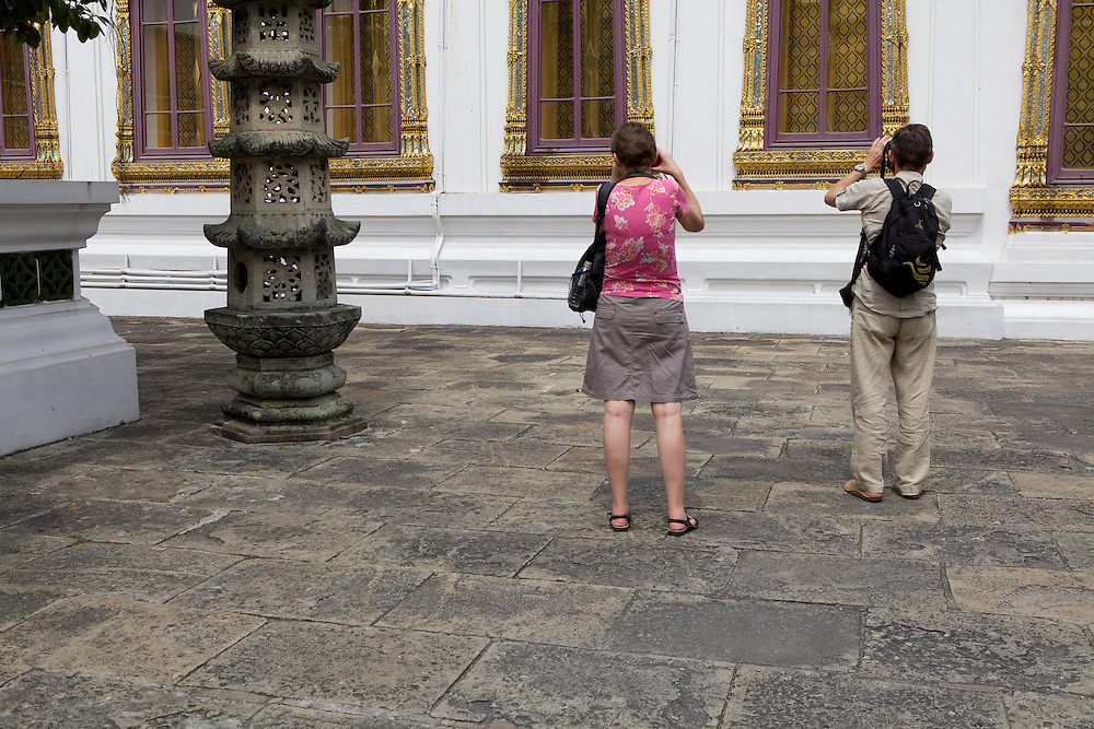 Tourists inside Wat Phra Kaeo (Temple of the Emerald Buddha) inside the grounds of the Grand Palace, Bangkok. Normally, palace entrance guards check every visitor's shoulders and knees to make sure that everyone is decently covered. This woman should have been turned back at the gate, so it's rare to see exposed knees inside the temple grounds.