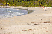 A woman walks along Red Beach (Playa Caracas) on Vieques Island, Puerto Rico.