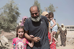 &copy; Licensed to London News Pictures. 15/06/2017. Mosul, Iraq. A Mosul resident cries as he and his family cross the last stretch of open ground watched by Islamic State snipers to reach Iraqi Army positions after escaping from ISIS held territory in West Mosul today (15/06/2017).<br /> <br /> Despite heavy fighting between the Islamic State and Iraqi Security Forces many civilians have started to leave ISIS territory in West Mosul. Mosul residents, many of whom have been in hiding in their homes since the start of the West Mosul Offensive, often have to run through ISIS sniper and machine gun fire to reach the safety of Iraqi Security Forces positions. Photo credit: Matt Cetti-Roberts/LNP