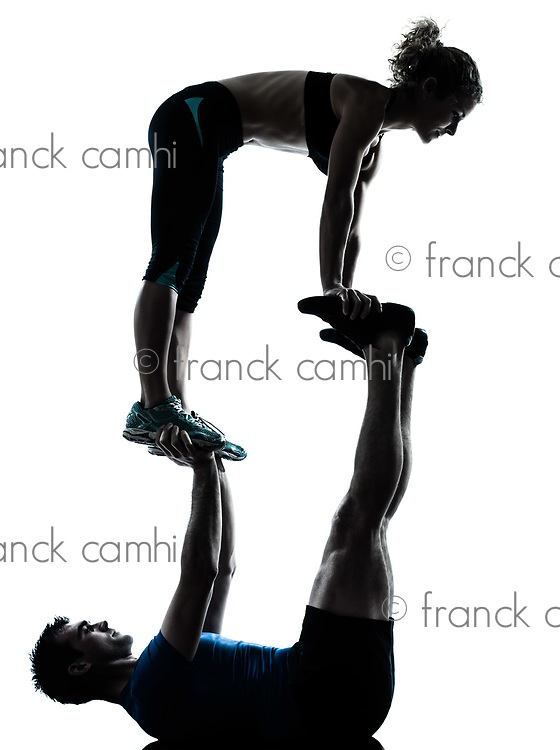 one caucasian couple man woman personal trainer coach exercising acrobatic silhouette studio isolated on white background