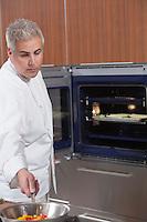 Mid- adult chef checks pan on hob