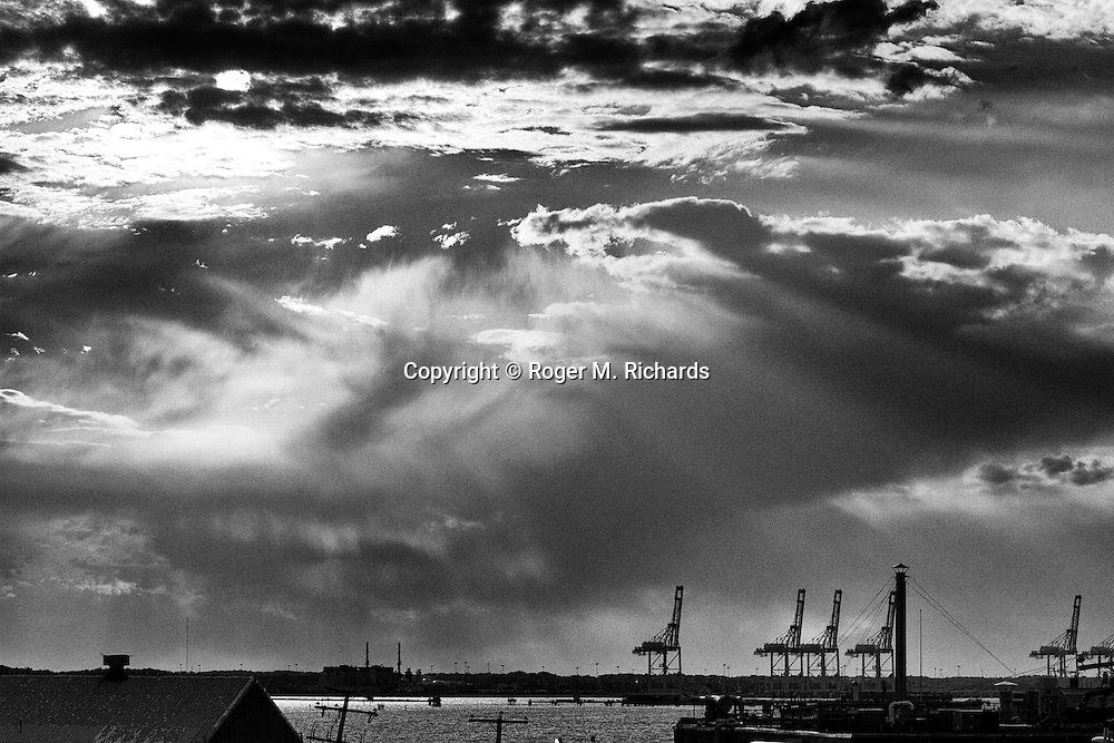A late afternoon sun peers through clouds over the piers where container ships are offloaded along the Elizabeth River in Norfolk and Portsmouth, Virginia. Coastal Virginia is one of the regions most affected by rising sea levels caused by climate change. This threatens both the economic and military stability of the area, as Norfolk-Virginia Beach-Newport News is home to both the largest military complex in the world, and a huge sea port that affects the economic health of sections of the eastern USA.