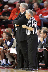 16 November 2014:  Stew Morrill stands next to referee Randy McCall watching a play during an NCAA non-conference game between the Utah State Aggies and the Illinois State Redbirds.  The Aggies win the competition 60-55 at Redbird Arena in Normal Illinois.