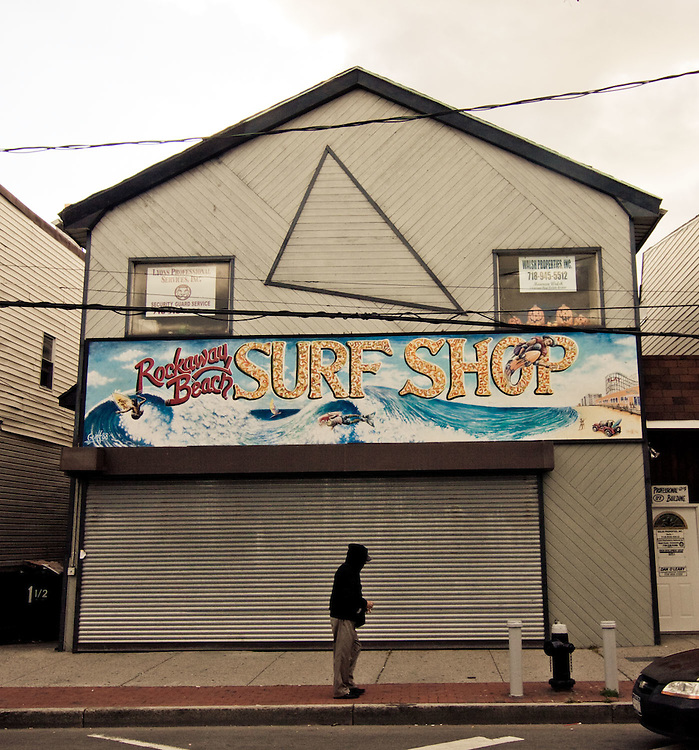 A man in a hoodie walks in front of the Rockaway Beach Surf Shop, Rockaway Beach, Queens, NY.