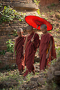Novice monks rwalking next to ancient stupas, Inle Lake, Burma