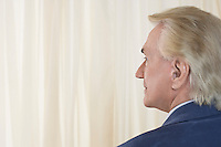 Senior Man in front of white curtain head and shoulders profile