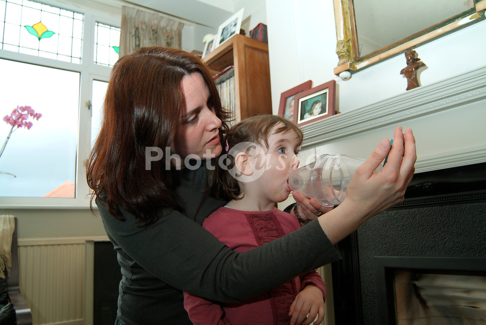 Mother helping 2 year old daughter with volumizer & blue inhaler; UK