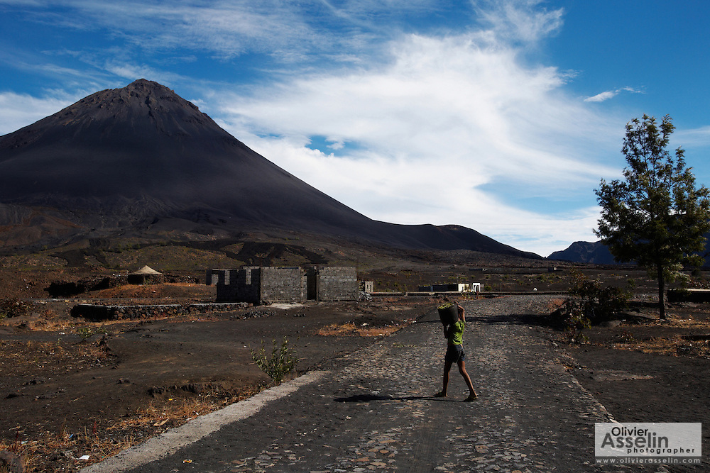 A child carrying a bucket full of beans walks across the street in the village of Portela, below Pico Fogo, the country's highest mountain, an active volcano towering at 2,829m (9,281 feet) in the Fogo national park on Fogo island, Cape Verde on Wednesday January 6, 2010..