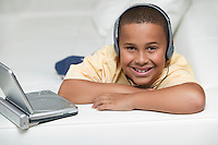 Boy on sofa Watching movie on Portable DVD Player portrait