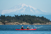 An adult couple paddle a kayak near Sucia island, a Washington state park, with Mount Baker seen in the background.