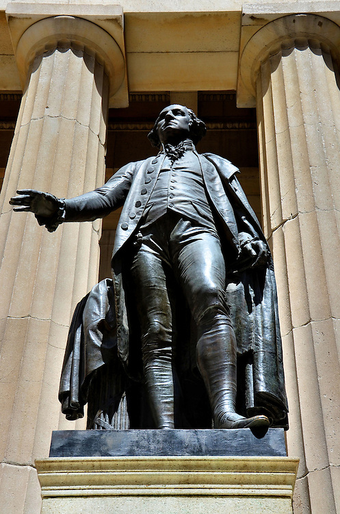 George Washington at Federal Hall Memorial at Wall Street in New York City, New York<br /> This George Washington statue between Doric columns commemorates his inauguration as the first president on April 30, 1789 at the Federal Hall balcony in New York City. That building was torn down in 1812, but the Federal Hall National Memorial was built in its place in 1842.  The bronze statue, which faces the New York Stock Exchange on Wall Street, was sculpted by John Quincy Adams Ward in 1882 and marks the spot of Washington&rsquo;s inauguration.