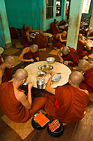 Monks eating lunch at the Kya Khat Winne Monastery, Bago, Myanmar (Burma)