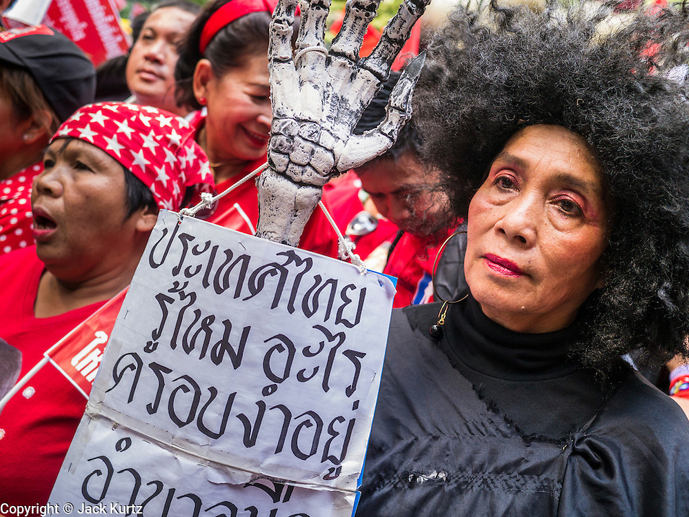 """10 DECEMBER 2012 - BANGKOK, THAILAND: Red Shirt protesters picket the Pheu Thai offices in Bangkok Monday. Although the Red Shirts support Pheu Thai, they are calling on the party to speed up constitutional reform. The Thai government announced on Monday, which is Constitution Day in Thailand, that will speed up its campaign to write a new charter. December 10 marks passage of the first permanent constitution in 1932 and Thailand's transition from an absolute monarchy to a constitutional monarchy. Several thousand """"Red Shirts,"""" supporters of ousted and exiled Prime Minister Thaksin Shinawatra, motorcaded through the city, stopping at government offices and the offices of the Pheu Thai ruling party to present demands for a new charter.         PHOTO BY JACK KURTZ"""