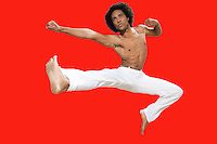Kickboxer jumping over red background