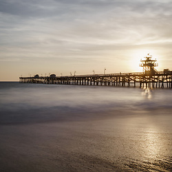 San Clemente pier sunset with the sun setting behind Lifeguard Tower Zero. San Clemente is a popular beach city along the Pacific Ocean in Orange County California. Photo is high resolution. Copyright ⓒ 2017 Paul Velgos with All Rights Reserved.