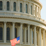 Dome of the US Capitol, with backlit American flag at half mast