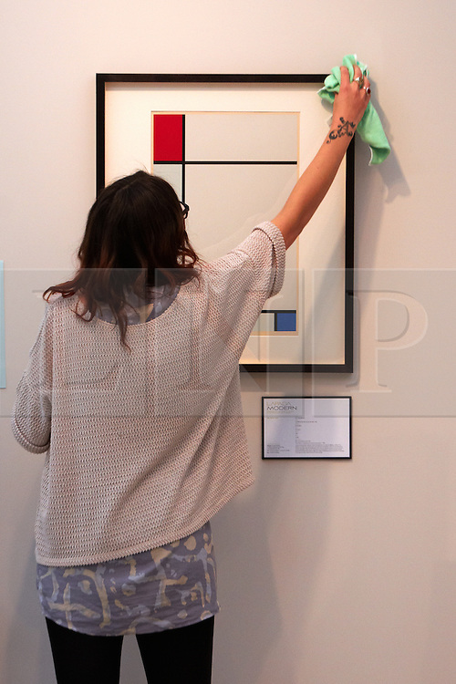 © licensed to London News Pictures. LONDON, UK  08/06/2011. Dealer Emily Wynne-Jones dusts a painting by Piet Mondriaan, worth £2,500, at the Olympia International Fine Art & Antiques Fair. All 30,000 items on sale from 150 dealers are vetted for authenticity by a panel of experts. The show opens in Olympia tomorrow (Thursday) and runs for 11 days. Please see special instructions for usage rates. Photo credit should read CLIFF HIDE/LNP