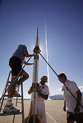 Amateur rocket launch.. Amateur rocketeers adjusting their rocket before launch. As another rocket launches in the background. At the annual Black Rock X amateur rocketry event in the Black Rock desert, Nevada, USA. This huge flat expanse of land is a popular launch site for large and powerful amateur rockets as it is far from civilization and has little natural animal or plant life.
