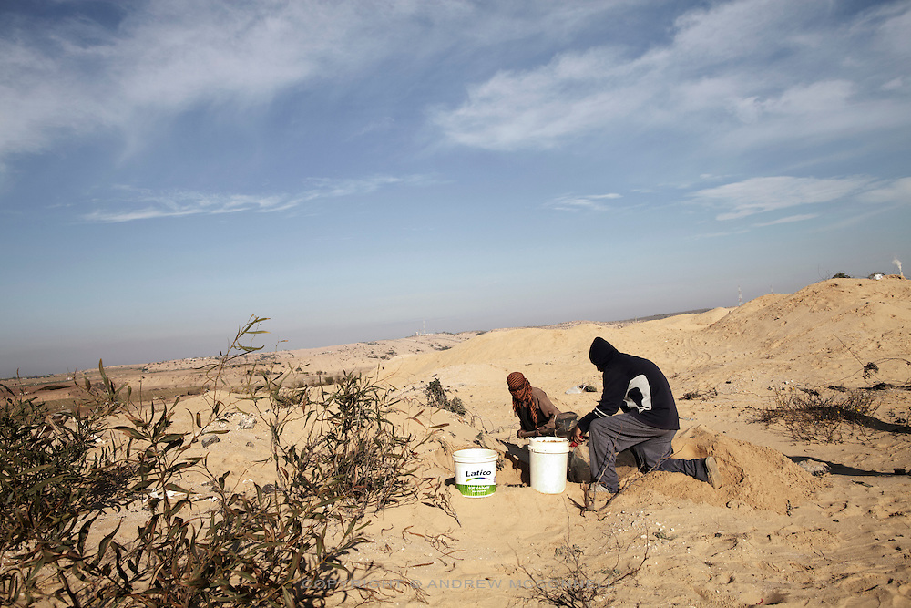 Men sieve sand for small stones beside Gaza's northern border. Under the blockade there is a severe lack of building materials in Gaza but the 300 meter buffer zone is a dangerous place to work, with dozens maimed and killed by Israel snipers.