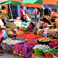 Women Shopping at El Mercado Farmers' Market in Antigua, Guatemala<br /> On the west side of town is the farmers' market called El Mercado. The front stalls have clothing and souvenirs for tourists. Keep walking into the bustling maze. Each step reveals more traditional and rustic displays of fruits, vegetables and flowers. You can also purchase fish, meat and pirated DVDs. Many vendors are inside a rudimentary concrete building. Others are crowded together outside. This scene of Guatemalan women haggling over the price of produce is typical. The market is open on Monday, Thursday and Saturday.