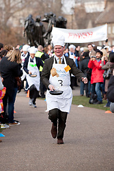 © Licensed to London News Pictures. 21/02/2012. LONDON, UK. Liberal Democrat MP Stephen Lloyd tosses a pancake as he takes part in a pancake race outside the Houses of Parliament today (21/02/12). Lords, Members of Parliament and political journalists today took part in the 2012 'Rehab Parliamentary Pancake Race' in aid of disability charity Rehab. The parliamentary team took the trophy after an extra lap was run due to widespread cheating. Photo credit: Matt Cetti-Roberts/LNP