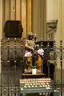 Nederland, Den Bosch, 20160723<br /> Beeld van Sint Anna en Jezus. Versierd met bloemen. Er branden kaarsjes voor.<br /> Kathedraal St. Jan in Den Bosch.De Sint-Janskathedraal (voluit: de Kathedrale Basiliek van Sint-Jan Evangelist) in de binnenstad van 's-Hertogenbosch wordt veelal beschouwd als het hoogtepunt van de Brabantse gotiek. De kathedraal imponeert door zijn omvang en enorme rijkdom aan beeldhouwwerk. Uniek in Nederland zijn de dubbele luchtbogen en uniek in de wereld zijn de 96 luchtboogfiguren.De kerk in volle pracht op de Parade<br /> Sint-Janskathedraal<br /> <br /> Netherlands, Den Bosch<br /> The St. John's Cathedral (in full: the Cathedral Basilica of St. John the Evangelist) in the city of 's-Hertogenbosch is often regarded as the pinnacle of Brabant Gothic. The cathedral impresses by its size and wealth of sculpture. Unique in the Netherlands are the double flying buttresses and unique in the world, the 96 flying buttress figures.<br /> St. John's Cathedral