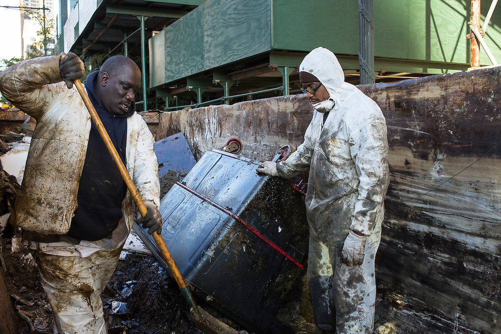 Workers empty trash bins filled with oil-soaked debris into a 30-cubic-yard roll-off trash container, their protective clothing soaked in oil. The smell of spilled oil permeates the air.