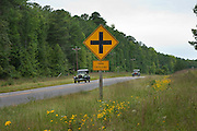 """Vintage autos pass by a """"Tank Crossing"""" sign on Route 40 at Fort Pickett. Dinwiddie County, on the South Side,  Virginia. NO PROPERTY RELEASE"""