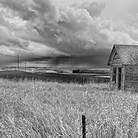 Grey clouds over open agricultural countryside with old shedRolette County
